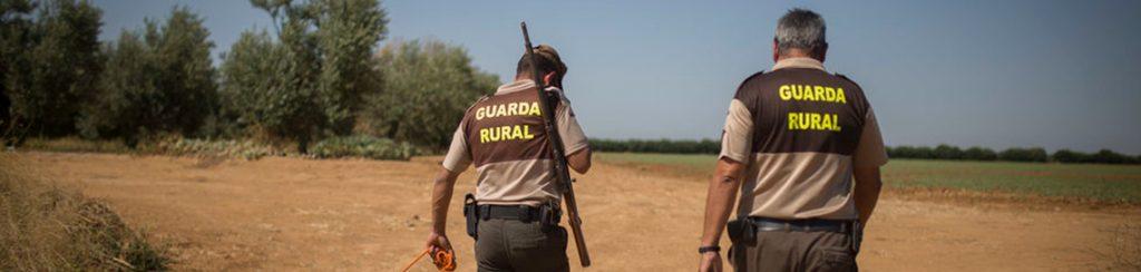 Dos guardas rurales armados paseando por un campo abierto